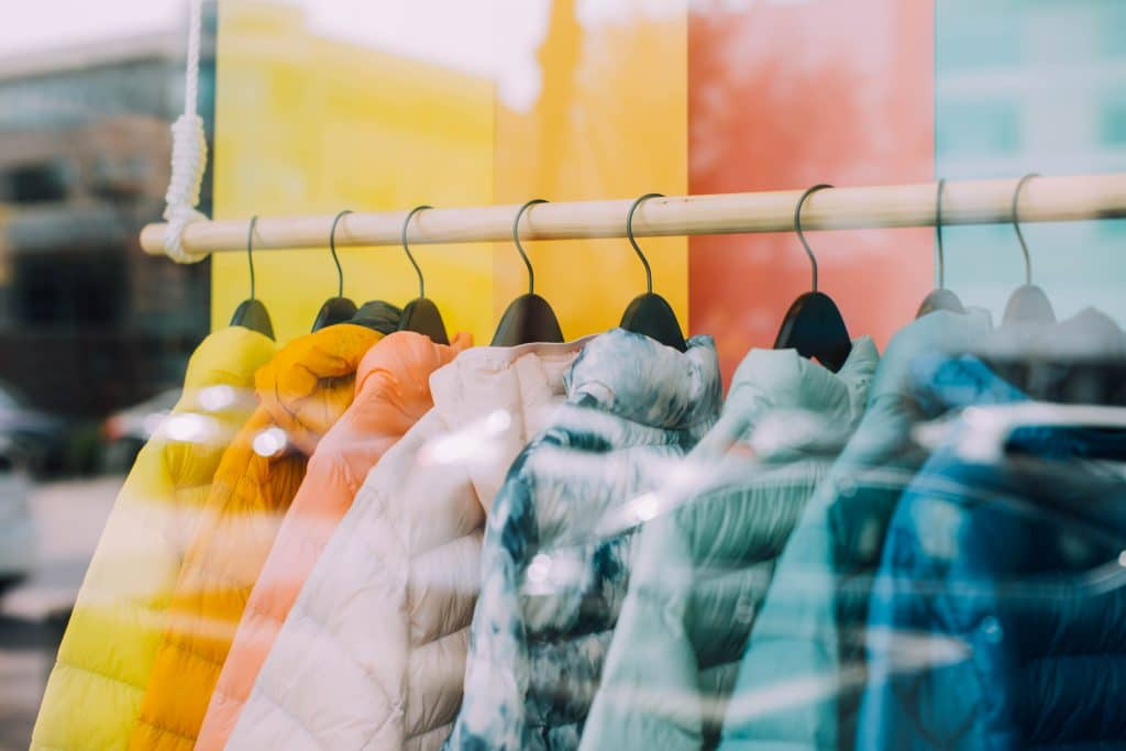 colourful coats on a clothing rack in a retail store.